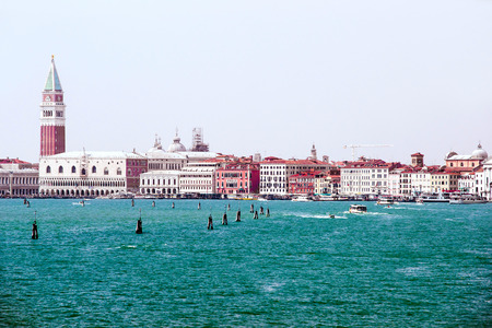 the campanile: Doges palace, campanile of St. Marco, St. Marco lion statue  and water traffic in summer Venice