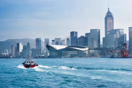 tug boat: Red tug boat in Victoria bay in front of Hong Kong skyline