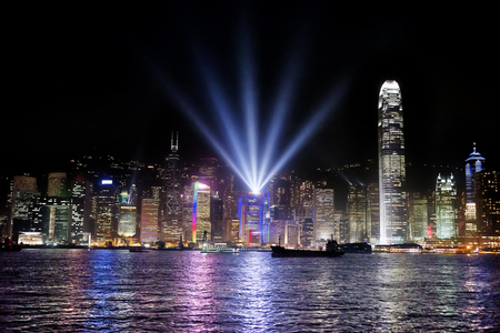 show time: Hong Kong bay and night skyline with cargo ship at symphony of lights show time Stock Photo
