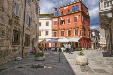 PULA, CROATIA - AUGUST 29, 2013: Street in old city center and people on the street in Pula