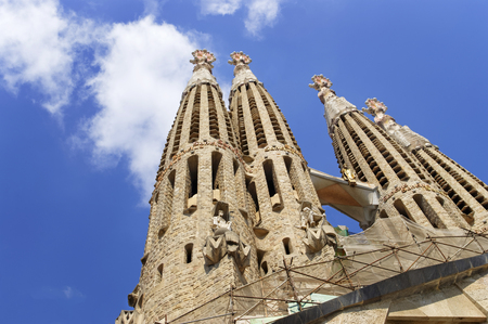 scaffolds: Towers of the Sagrada Familia Cathedral in Barcelona in front of blue sky with clouds