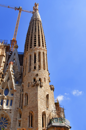 scaffolds: Tower of the Sagrada Familia Cathedral in Barcelona in front of blue sky with clouds