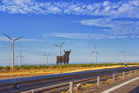 weather front: Wind turbines and black bull shape in front of blue sky at summer sunny weather in Spain view from highway Stock Photo