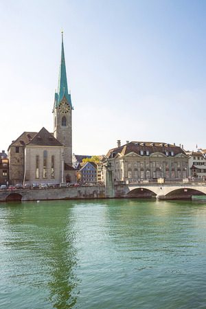 spire: Zurich city center and Limmat quay in summer with city hall clock tower spire in summertime