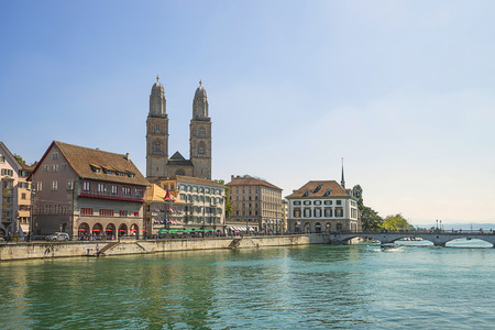 spires: Zurich city center and Limmat quay in summer with Cathedral and city hall clock towers spires in summer Stock Photo