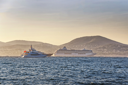 cruise liner: Cruise liner and luxury yachts in Saint Tropez harbor in sun rays at sunset