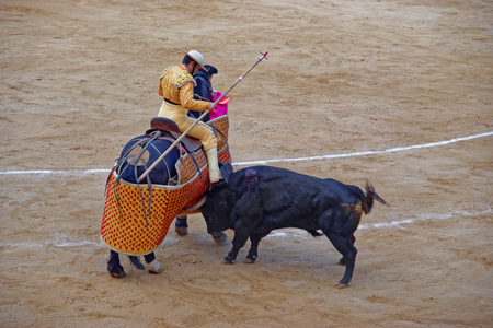 attacking: BARCELONA, SPAIN - AUGUST 01, 2010:  Bull is attacking the bullfighter during a bullfight in one of the larger public arenas in Barcelona - the Plaza Monumental de Barcelona, known simply as La Monumental Editorial