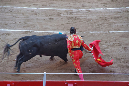 corrida: Bullfighter and a bull in one of the largest arenas in Barcelona during a Spanish national entertainment - corrida bullfighting. La Monumental bullring arena. Barcelona, Catalonia, Spain