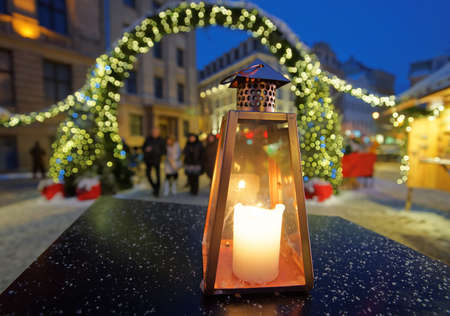 in europe: Lantern on a table on the background of the Christmas market in Riga Dome square Latvia Stock Photo