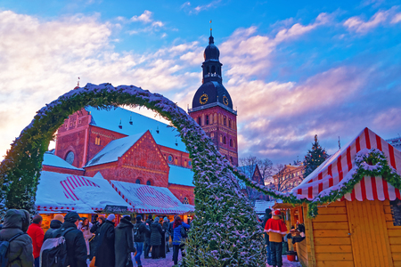 advent time: RIGA, LATVIA - DECEMBER 28, 2014: Unidentified group of people enjoy Christmas market in Rigas Old Town, Latvia. It attracts more than 750 thousands of visitors during the whole advent time.