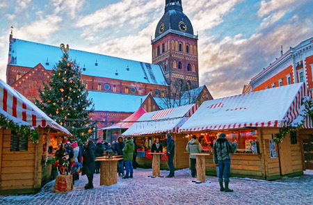 deemed: RIGA, LATVIA - DECEMBER 28, 2014: Christmas market at Dome square in Old Riga Litvia. Dome Square is the largest square in the Old Town. It is deemed to be the heart of the city.