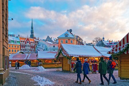 held down: RIGA, LATVIA - DECEMBER 28, 2014: People stroll down an aisle at the Christmas Market held at Rigas Old Town Dome square on December 28, 2014. Latvia
