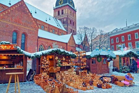 a straw: Traditional Christmas market stall with straw basket souvenirs displayed for sale in the Old Town of Riga, Latvia Stock Photo