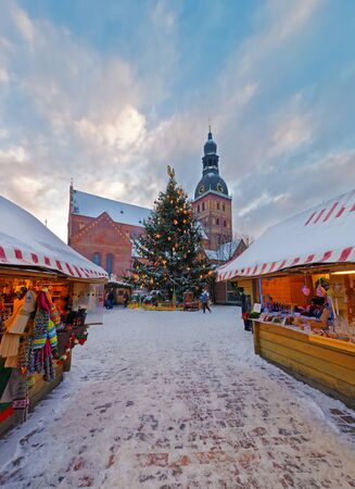 traditional goods: Christmas Markets in Riga Latvia with a beautiful Christmas tree and stalls loaded with traditional goods for sale. Riga claims to be home of the first Christmas tree. Stock Photo