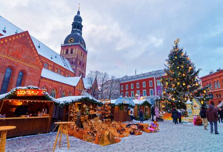 fair: Beautiful snowy winter scenery of Christmas holiday fair at Dome Square in Rigas Old Town, Latvia Editorial