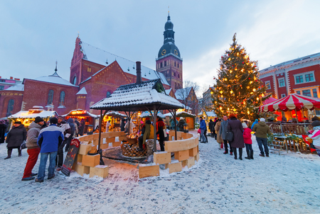 snow scene: RIGA, LATVIA - DECEMBER 28, 2014: Unidentified group of people enjoy Christmas market held at Old Towns Dome Square, Riga, Latvia. Riga is thought to be the City where the tradition of decorating the Christmas Tree started