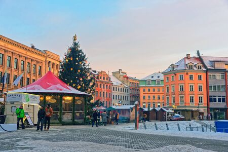 traditional goods: European Christmas Market in Riga (Latvia) with a beautifully decorated fir tree and stalls loaded with traditional goods for sale Editorial