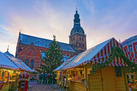 Group of unidentified people enjoy traditional Christmas market at Dome square in Old Town of Riga, Latvia
