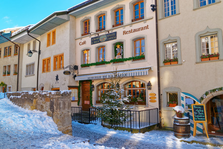 gruyere: GRUYERE; SWITZERLAND - DECEMBER 31, 2014: Medieval town of Gruyeres, Fribourg canton, Switzerland on a beautiful sunny winter day. Gruyere is a famous tourist destination and also know for its cheese Editorial