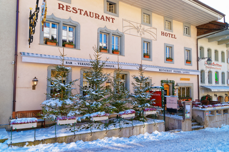 gruyere: GRUYERE, SWITZERLAND - DECEMBER 31, 2014: Cozy restaurant in the swiss village Gruyeres, Switzerland. The most popular Swiss dishes are fondue and raclette with Swiss Cheese called Gruyere Editorial