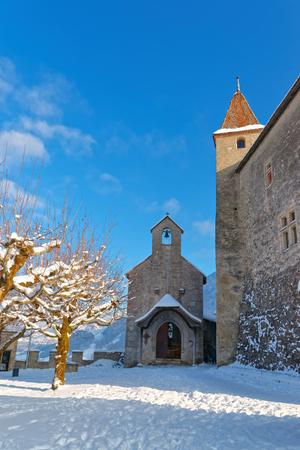 dinky: GRUYERE, SWITZERLAND - DECEMBER 31, 2014: Dinky little chapel in front of the castle of Gruyeres in Switzerland on a beautiful winter day. Editorial