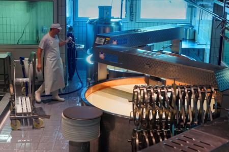 queso: GRUYERE, SUIZA - 31 de diciembre, 2014: Cheesemaker est� en el trabajo durante la tramitaci�n del legendario queso gruyere en la f�brica de queso Maison du Gruy�re en Suiza