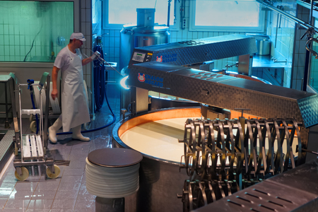 cows milk cheese: GRUYERE, SWITZERLAND - DECEMBER 31, 2014: Cheesemaker is at work during the processing of the legendary Gruyere cheese at the Maison du Gruyere cheese factory in Switzerland Editorial
