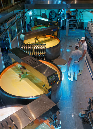 gruyere: GRUYERE, SWITZERLAND - DECEMBER 31, 2014: Gruyere cheese processing. It is a hard yellow cheese, named after the town of Gruyeres in the canton of Fribourg, Switzerland Editorial