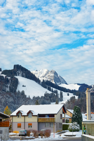 gruyere: Small town of Gruyere covered in snow with the Swiss mountains in the background. Gruyeres is a famous Swiss tourist destination and gives its name to the well-known Gruyere cheese Editorial