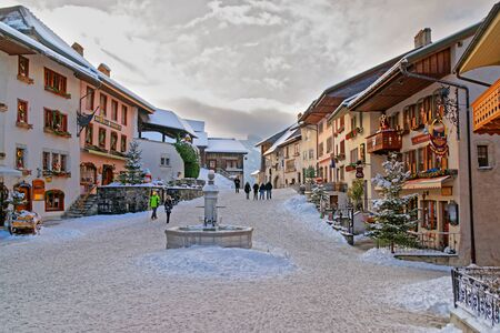 gruyere: GRUYERE, SWITZERLAND - DECEMBER 31, 2014: Winter view of the market place in the center of Gruyeres. It is a famous tourist destination in Switzerland and gives its name to well-known Gruyere cheese Editorial