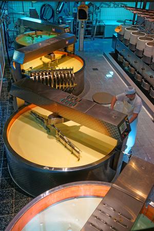 queso: GRUYERE, SUIZA - 31 de diciembre 2014: El procesamiento de leche fresca en queso. Gruyere f�brica de queso en los Gruy�res hist�ricos de las ciudades, en el cant�n de Friburgo, Suiza Editorial