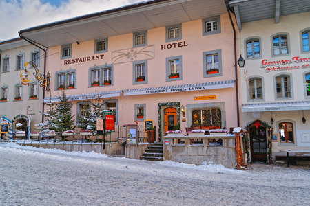 is well known: GRUYERE, SWITZERLAND - DECEMBER 31, 2014:  Exterior of the restaurant serving traditional Swiss cuisine in Gruyere, Switzerland. Gruyeres is a famous tourist destination well known for its cheese Editorial