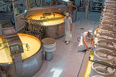 gruyere: GRUYERE, SWITZERLAND - DECEMBER 31, 2014: Production of Gruyere cheese at the cheese-making factory of Gruyeres, canton of Fribourg, Switzerland