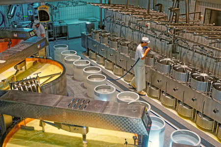 gruyere: GRUYERE, SWITZERLAND - DECEMBER 31, 2014: Worker of the cheese-making factory of Gruyeres cleaning cheese molds. Gruyere is a famous swiss cheese generally known as one of the best cheeses for baking