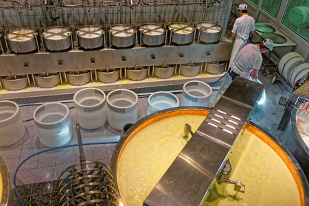 gruyere: GRUYERE, SWITZERLAND - DECEMBER 31, 2014: Important stage of Gruyere cheese production, when the as-yet-undrained curd is broken by rotating mixers Editorial