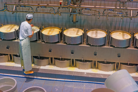 gruyere: GRUYERE, SWITZERLAND - DECEMBER 31, 2014: Worker of the cheese making factory concentrated on the process of production of Gruyere cheese