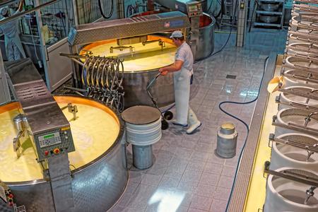 gruyere: GRUYERE, SWITZERLAND - DECEMBER 31, 2014: Worker of Gruyere cheese factory during industrial production of well-known Gruyere cheese