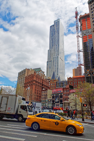 ongoing: Typical New York City street view with a yellow taxi, passing by pedestrians, ongoing construction works and a skyscraper, rising to the sky