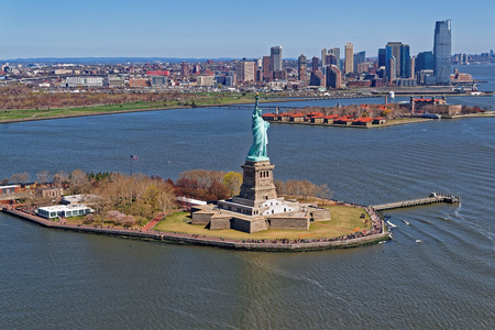 statue: Aerial view of the Statue of Liberty in New York City, USA with Downtown Brooklyn and Governors island in the background. The statue is an icon of freedom and of the United States Stock Photo