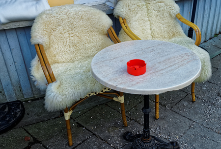 sheepskin: Couple of wicker chairs covered with sheepskin and a table in front of the building in Garmisch-Partenkirchen. It is a mountain resort town in Bavaria, southern Germany, in the heart of the Alps