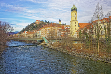 GRAZ, AUSTRIA - JANUARY 7, 2014: River view to the Franciscan church and Clock tower of the Castle Hill in Graz of Austria in January