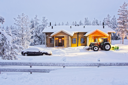 clear away: Tractor is clearing away snow at the Wooden Cottage in Ruka in Finland in the Arctic pole circle in winter Editorial