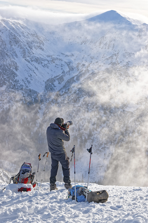 winter photos: Man taking photos at top of Kasprowy Wierch of Zakopane in winter. Zakopane is a town in Poland in Tatra Mountains. Kasprowy Wierch is a mountain in Zakopane and is the most popular ski area in Poland