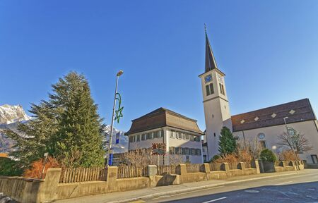 st gallen: Catholic Church and Mountains in Bad Ragaz. Bad Ragaz is a city in canton St. Gallen in Switzerland.  It lies over Graubunden Alps. Spa and recreation village is at end of Tamina valley
