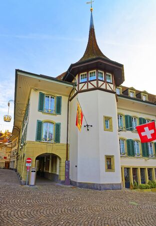 crown spire: Krone Hotel and Flags in the Town Hall Square of Thun. Thun is a city in Swiss canton of Bern, where Aare river flows out of Lake Thun. Town Hall Square is a historic center of the city Editorial