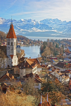 Panorama of City Church and City of Thun with Alps and Thunersee. Thun is a city in the canton of Bern in Switzerland, where the Aare river flows out of Lake Thun. There is a view of Bernese Alps.