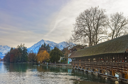 out of town: Old Wooden Sluice bridge in the Old Town of Thun. Thun is a city in Swiss canton of Bern, where Aare river flows out of Lake Thun. Stock Photo