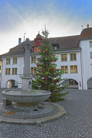 town hall square: Rathaus hotel, Christmas tree and Fountain in Thun Town Hall Square. Thun is a city in Swiss canton of Bern, where Aare river flows out of Lake Thun. Town Hall Square is a historic center of the city
