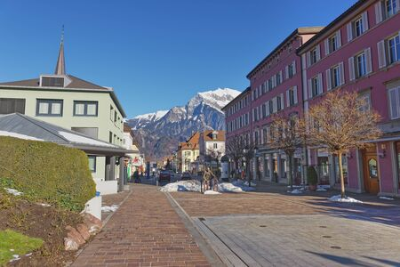 st gallen: BAD RAGAZ, SWITZERLAND - JANUARY 5, 2015: Monument of Sitting Man and Alps Mountains. Bad Ragaz is a city in St. Gallen in Switzerland, over Graubunden Alps. Spa and recreation is at the Tamina valley Editorial
