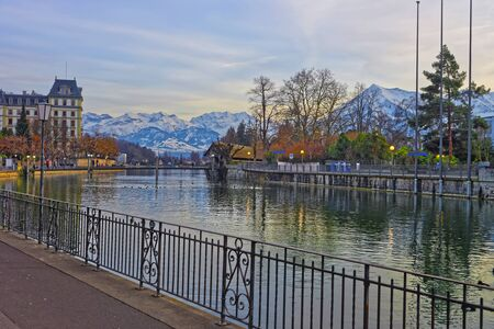 out of town: Embankment and mountains in Old Town of Thun. Thun is a city in Swiss canton of Bern. It is located where Aare river flows out of Lake Thun. Stock Photo